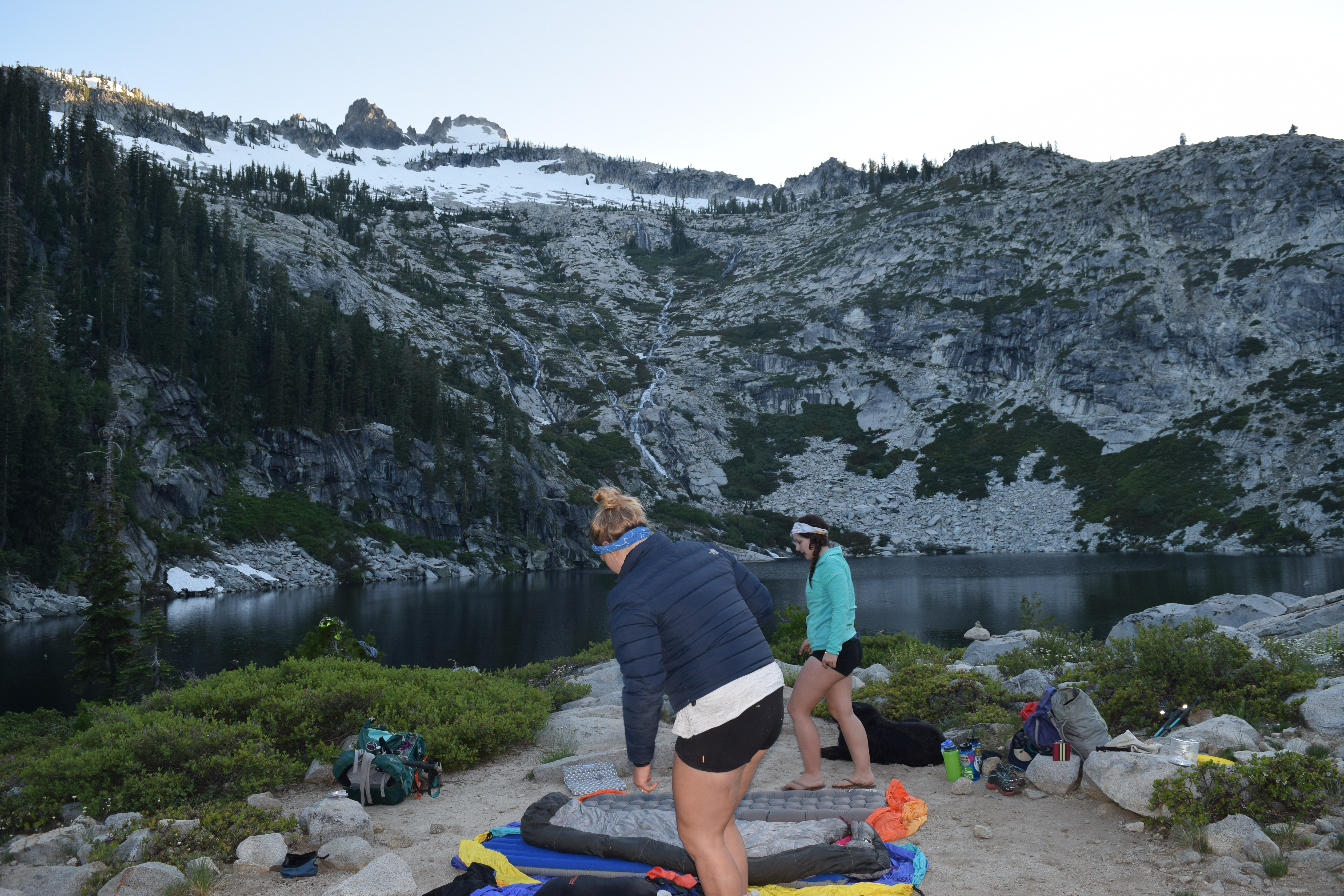 Two woman setting up a campsite overlooking a small lake in a mountain basin.