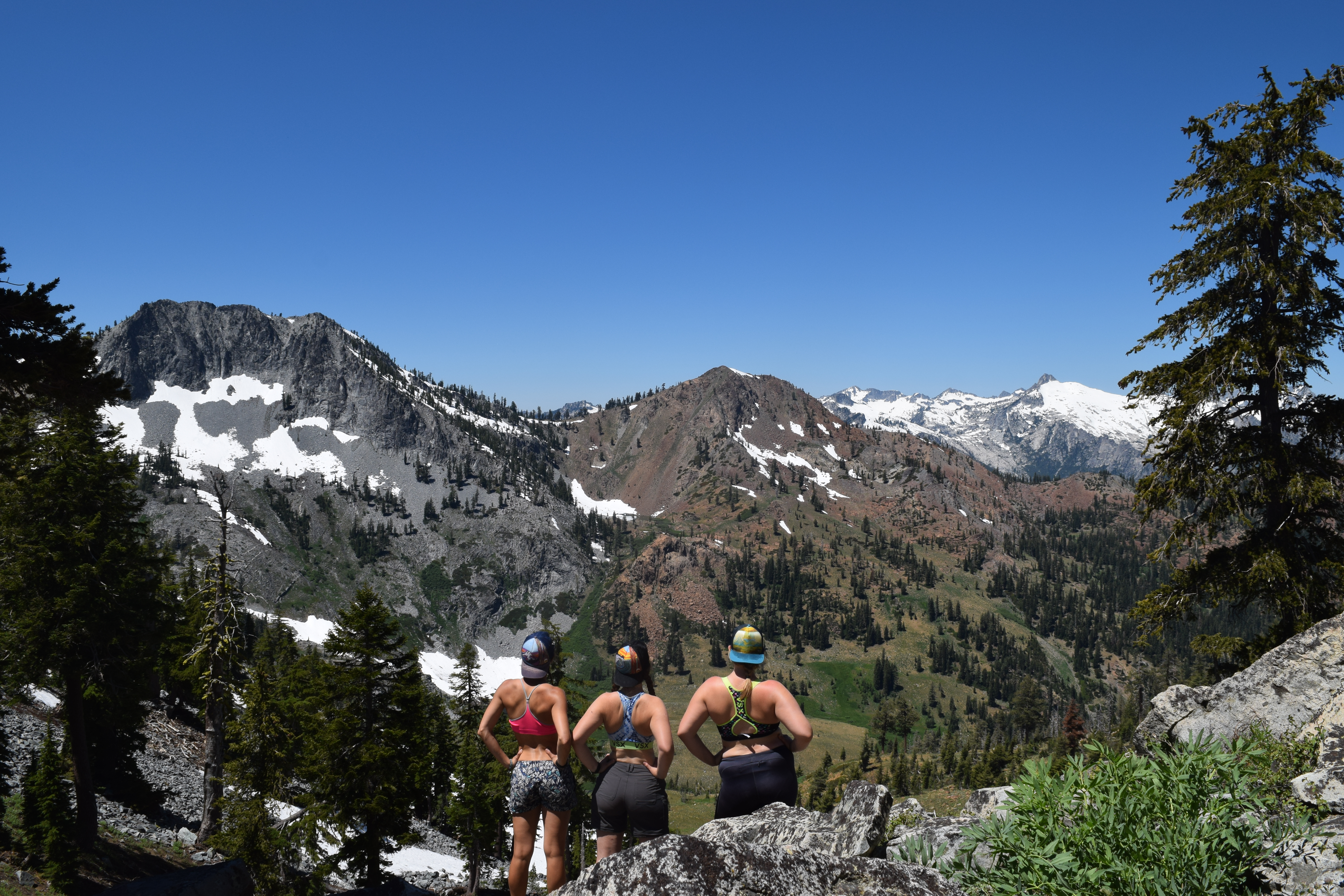 Three women in sports bras and shorts, looking out at a mountain basin whose rock types correspond very well to the above geologic map.