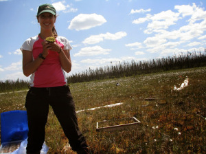 Woman standing in a wetland, grinning and holding out a handful of peat moss