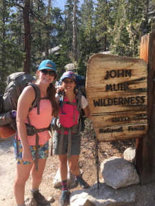 Two women wearing backpacking backpacks, smiling at the signpost to the John Muir Wilderness in California